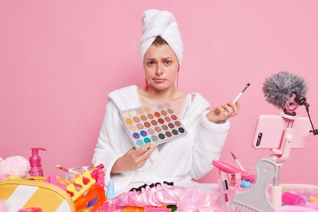 Frau in weißem bademantel und handtuch hält lidschatten-palette und kosmetikpinsel, die über make-up an abonnenten einzeln auf rosa ausstrahlen.