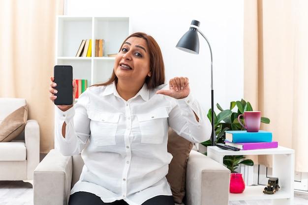 Frau in weißem hemd und schwarzer hose, die das smartphone zeigt, das mit dem zeigefinger darauf zeigt, lächelnd auf dem stuhl im hellen wohnzimmer sitzend