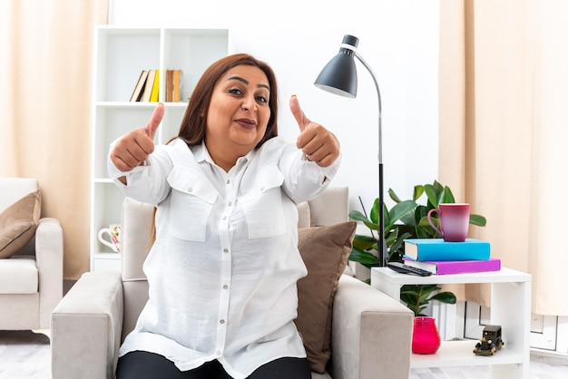 Frau in weißem hemd und schwarzer hose, die glücklich und fröhlich aussieht und daumen nach oben auf dem stuhl im hellen wohnzimmer zeigt