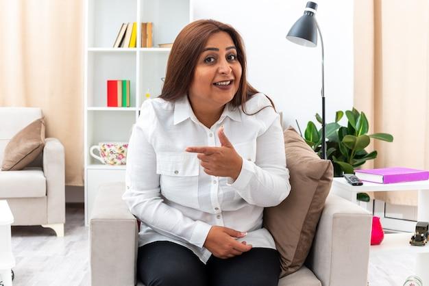 Frau in weißem hemd und schwarzer hose, die glücklich und positiv lächelt und mit dem zeigefinger auf die seite zeigt, die auf dem stuhl im hellen wohnzimmer sitzt