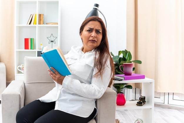 Frau in weißem hemd und schwarzer hose liest ein buch mit ernstem gesicht, während sie auf dem stuhl im hellen wohnzimmer sitzt living