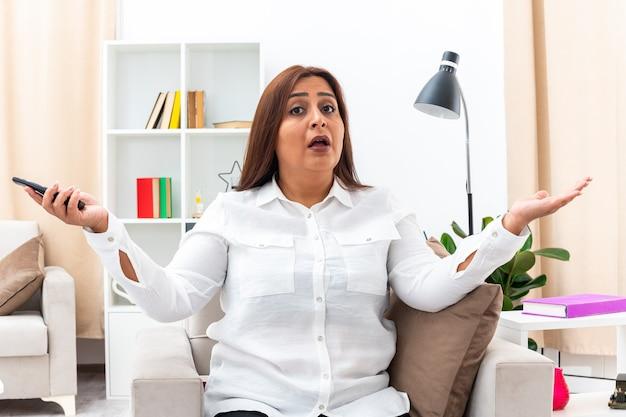 Frau in weißem hemd und schwarzer hose mit tv-fernbedienung, die verwirrt aussieht und die arme zu den seiten ausbreitet, sitzt auf dem stuhl im hellen wohnzimmer