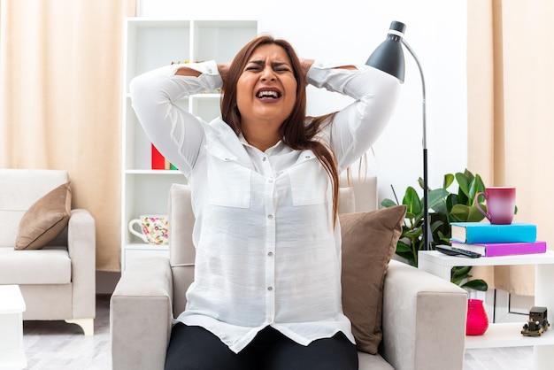 Frau in weißem hemd und schwarzer hose schreit wild frustriert und verrückt mit den händen auf dem kopf auf dem stuhl im hellen wohnzimmer sitzend