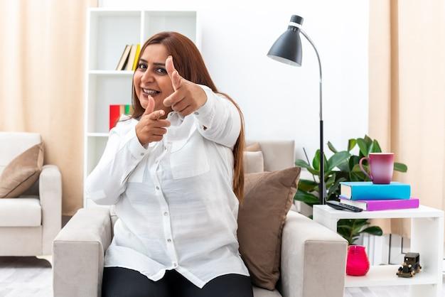 Frau in weißem hemd und schwarzer hose sitzt auf dem stuhl und lächelt fröhlich und zeigt mit dem zeigefinger im hellen wohnzimmer living