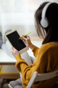Frau in weißen drahtlosen kopfhörern hält weißes tablett mit stift. home office während der selbstisolation, arbeiten von zu hause aus. online-bildung, e-learning während der quarantäne.