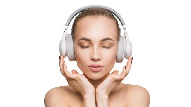 Frau in weißen kopfhörern auf weißer wand hört musik mit geschlossenen augen.
