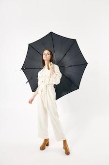 Frau in weißen overalls-modestiefeln öffnen regenschirmschutz vom regenstudio