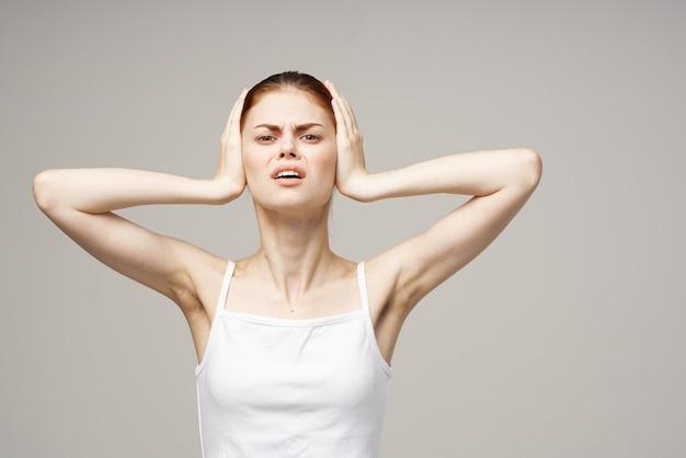 Frau in weißen t-shirt emotionen missfallen ohr probleme studio