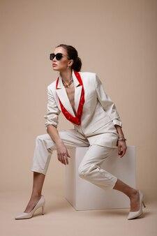 Frau in weißer anzugjacke hose schuhe rote accessoires sonnenbrille auf beige pudrigem hintergrund