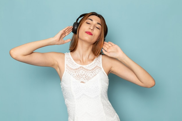 Frau in weißer bluse und blue jeans musik hören