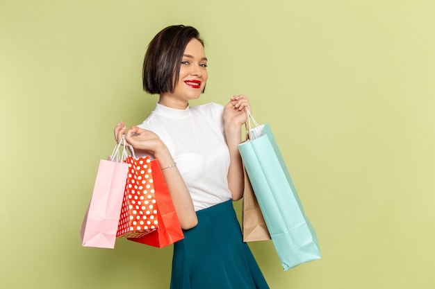 Frau in weißer bluse und grünem rock hält einkaufspakete und lächelt