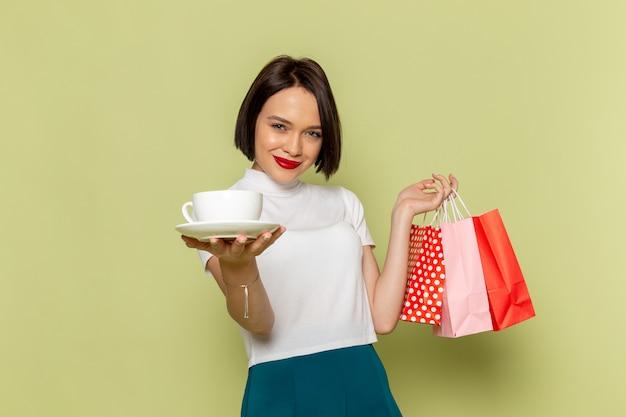 Frau in weißer bluse und grünem rock hält einkaufspakete und weiße tasse