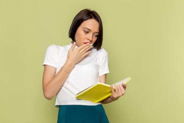 Frau in weißer bluse und grünem rock hält und liest buch