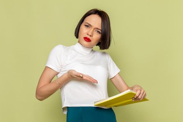 Frau in weißer bluse und grünem rock hält und liest gelbes buch