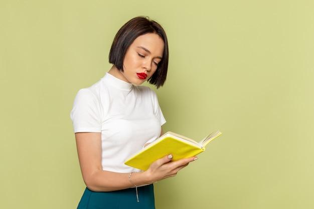 Frau in weißer bluse und grünem rock liest ein buch