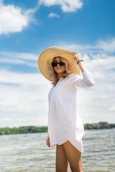 Frau in weißer bluse und strohhut ruht an einem heißen sommertag auf dem see