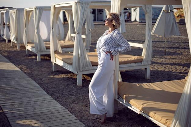 Frau in weißer kleidung und sonnenbrille steht am strand in der nähe von holz