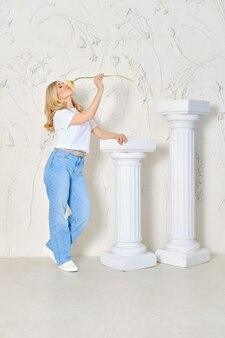 Frau in weiten jeans und unterhemd steht mit blume in der hand in der nähe der dekorativen säule