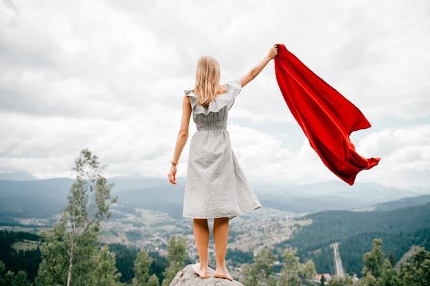 Frau in wilden bergen gibt notsignal sos mit roter abdeckung. konzept der notsituation während der wanderung in den bergen. barfuß frau steht am stein, winkt rote decke und wartet auf hilfe