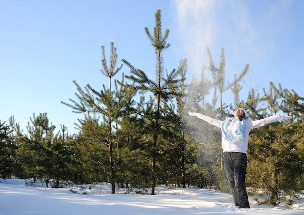 Frau in winterkleidung gekleidet, steht zwischen kiefern und wirft schnee. foto in voller höhe, hände erhoben