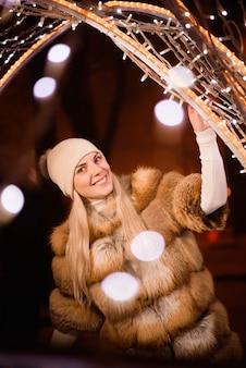 Frau in winterkleidung über verschwommene lichter in der nähe