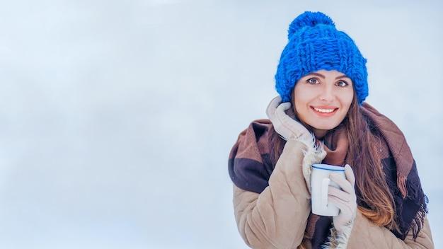 Frau in wintermütze und eine tasse in der hand