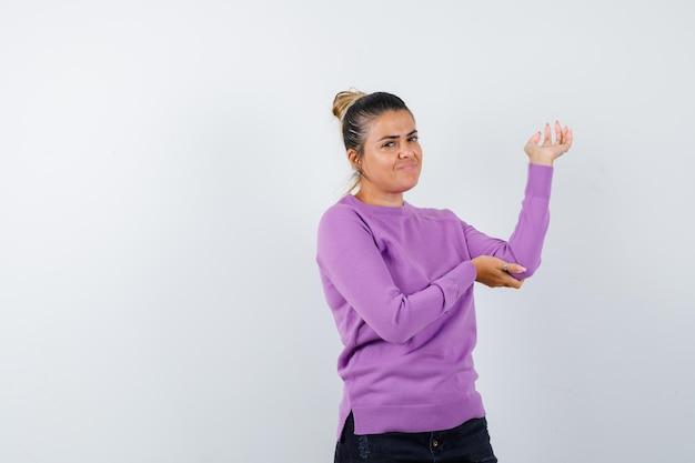 Frau in wollbluse, die etwas zeigt oder einladend und fröhlich aussieht
