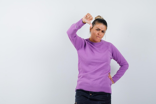 Frau in wollbluse zeigt daumen nach unten und sieht enttäuscht aus