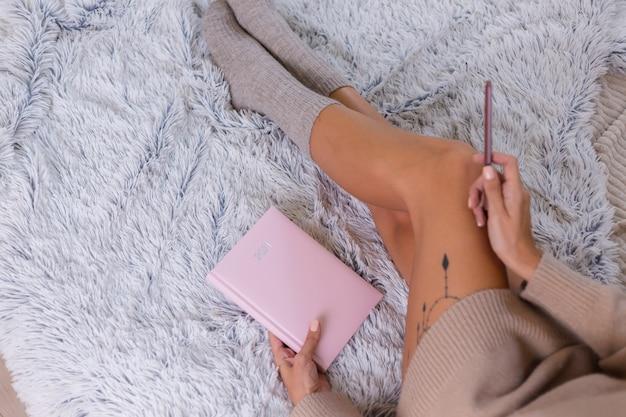 Frau in wollsocke und -pullover mit rosa notizbuchzeichen 2021, großes tattoo auf hüfte. frau sitzen zu hause im schlafzimmer auf dem bett.