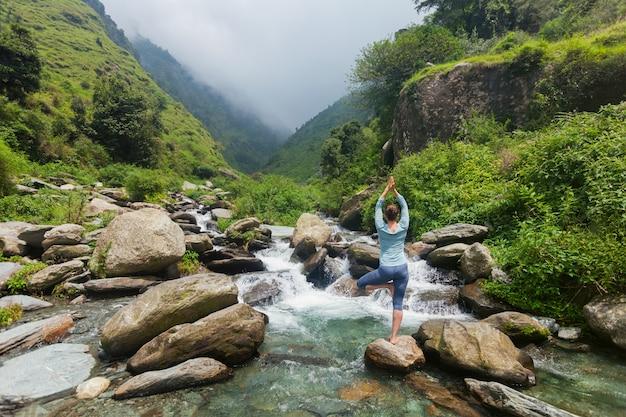 Frau in yoga asana vrikshasana baum pose am wasserfall im freien