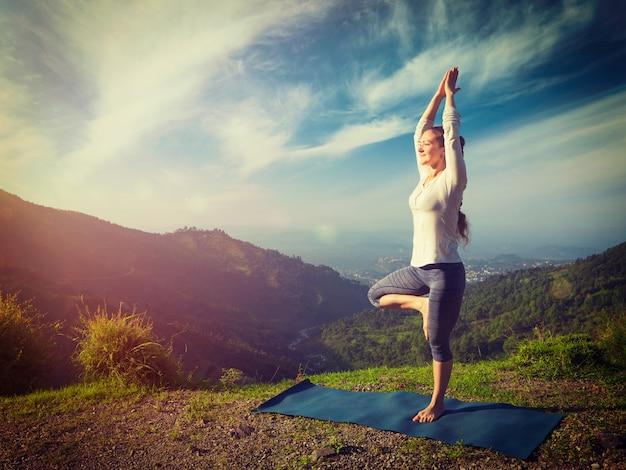Frau in yoga asana vrikshasana baum pose in bergen im freien