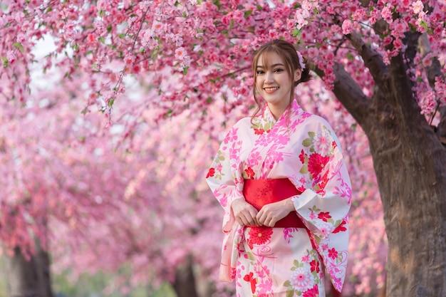 Frau in yukata (kimonokleid), die sakura-blume oder kirschblüte schaut, die im garten blüht