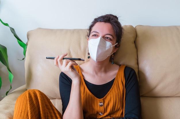Frau infiziert mit coronavirus-krankheit, die einen freund mit telefon anruft. zu hause bleiben. pandemieviruskrankheit covid 19.