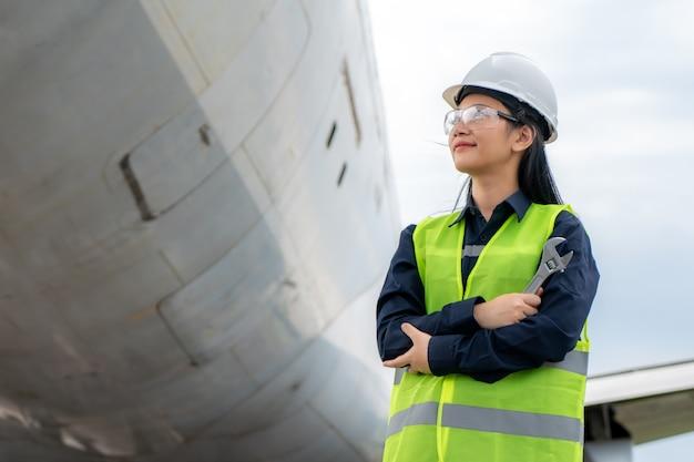 Frau ingenieur wartung flugzeug arm gekreuzt und hält schraubenschlüssel im vorderen flugzeug von reparaturen
