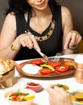 Frau isken iskender kebab unter verwendung von gabel und messer