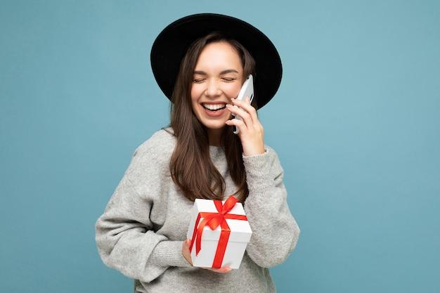 Frau isoliert über blaue hintergrundwand, die schwarzen hut und grauen pullover hält, der geschenkbox hält, der auf handy spricht und lacht.