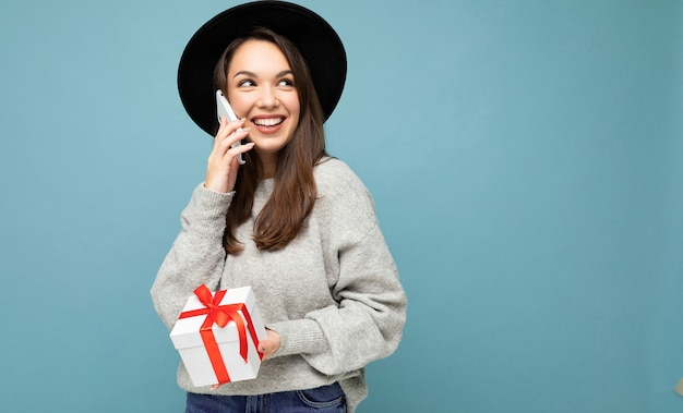 Frau isoliert über bunte hintergrundwand, die stilvolle freizeitkleidung hält, die geschenkbox hält und zur seite schaut. freiraum