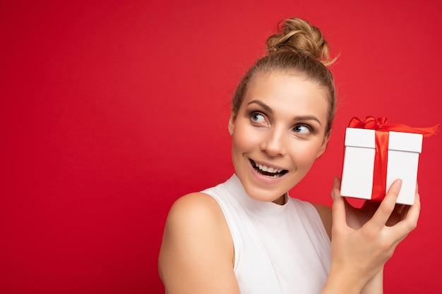 Frau isoliert über bunte hintergrundwand, die stilvolle freizeitkleidung hält, die geschenkbox hält und zur seite schaut. speicherplatz kopieren, modell
