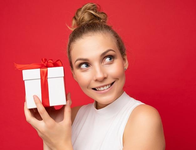 Frau isoliert über bunte hintergrundwand, die stilvolle freizeitkleidung hält, die geschenkbox hält und zur seite schaut. speicherplatz kopieren