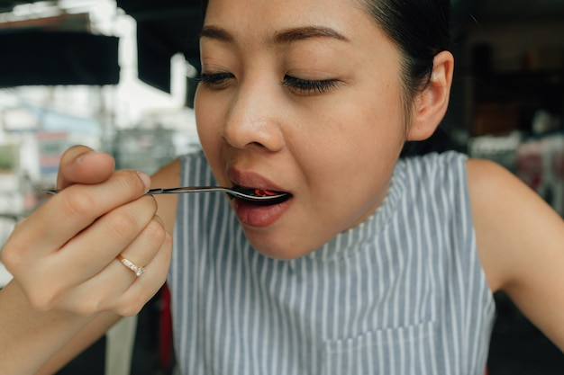 Frau isst angebratenes schweinefleisch und basilikum des thailändischen reises.