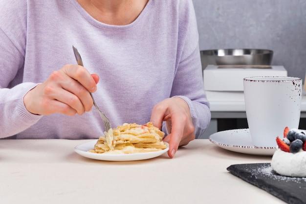 Frau isst dessert und trinkt kaffee oder tee. nahansicht.
