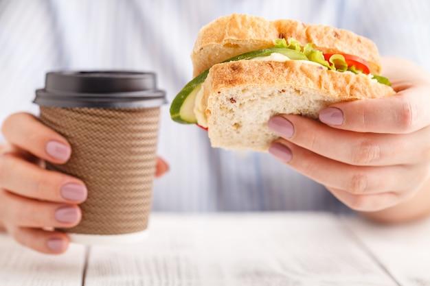 Frau isst ein großes sandwich mit fleisch und wegetables