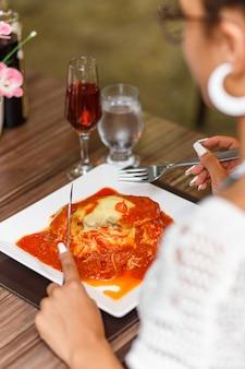 Frau isst ein köstliches gericht aus fleisch und nudeln parmigiana.
