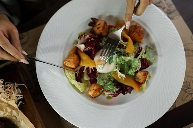 Frau isst einen salat von frischem gemüse mit blättern von grünem salat und frischem gelbem pfeffer mit fischstücken und einem pochierten ei in einem restaurant. nahansicht nahaufnahme. gesundes frühstück