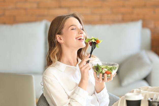 Frau isst gesunden gemüsesalat im büro eating