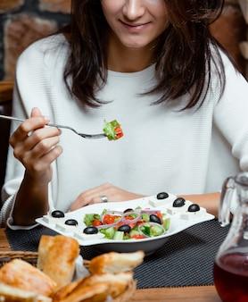 Frau isst griechischen salat mit tomaten, zwiebeln