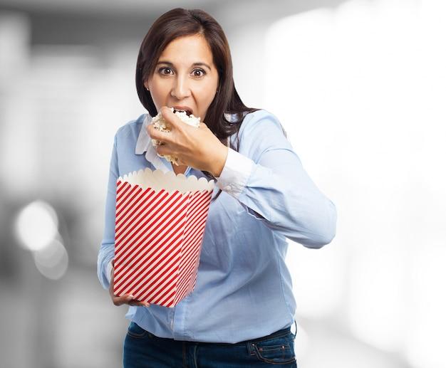 Frau isst popcorn mit verlangen