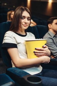 Frau isst popcorn, während sie film im kino sieht