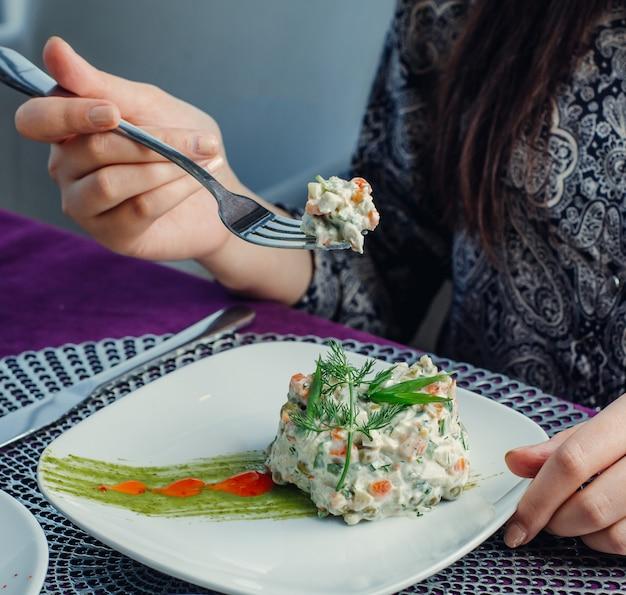 Frau isst portionierten oliviersalat mit dill an der spitze im restaurant