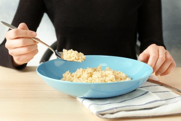 Frau isst quinoa-brei am küchentisch